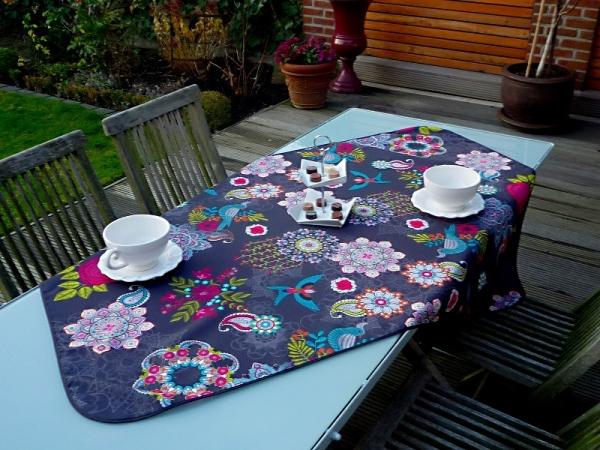 Farbspektakel – Schwarze Tischdecke mit schillernden Blumen und Vögeln